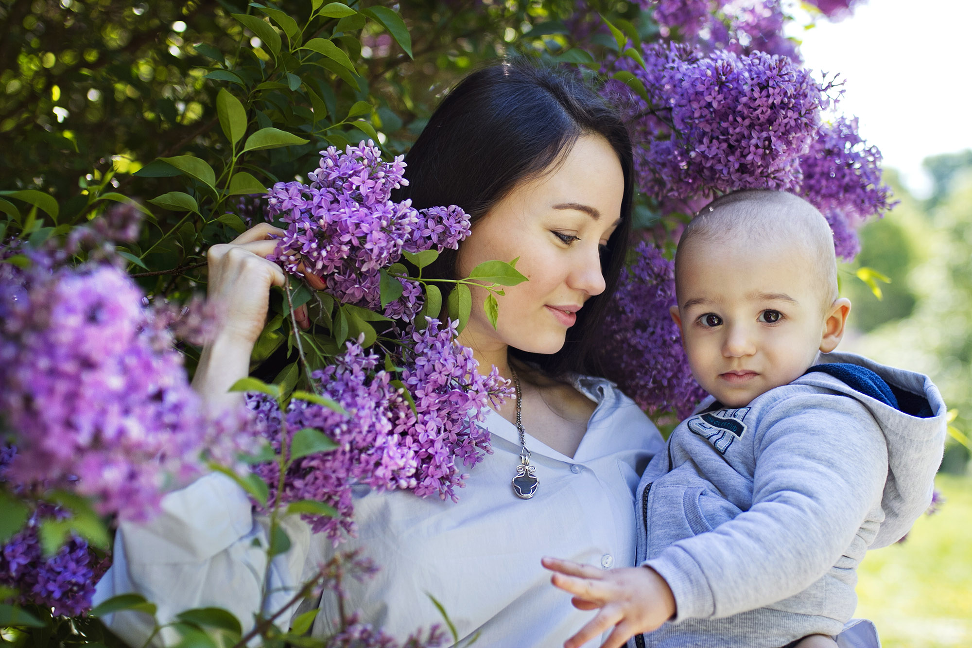 Mother with her small son in flowers