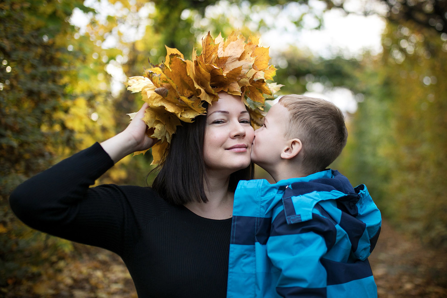 Mother wearing leaf wreath with her son