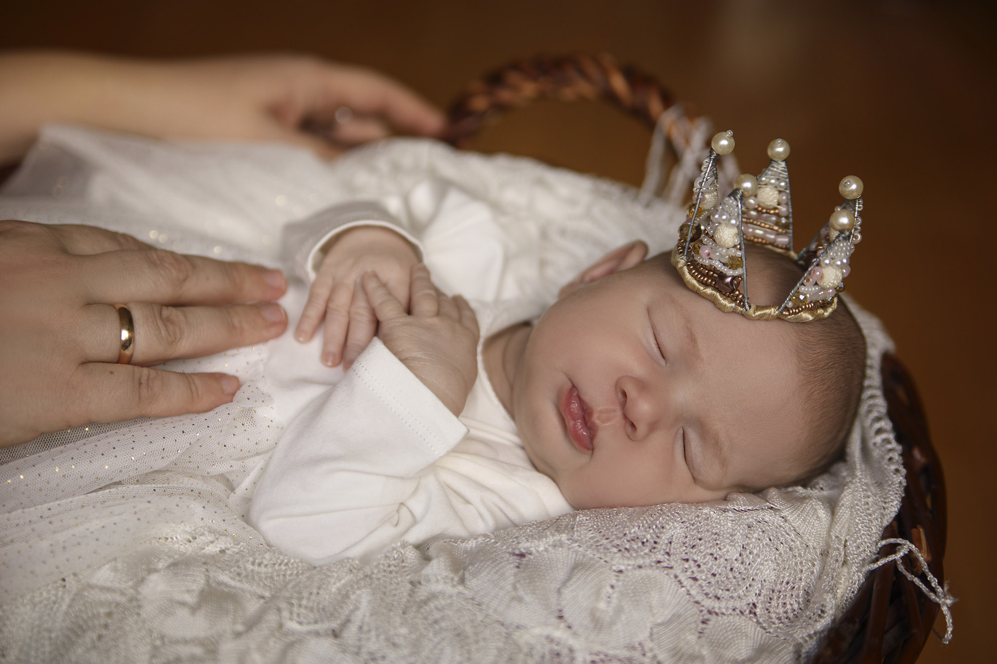 Sleeping infant in a basket with a crown
