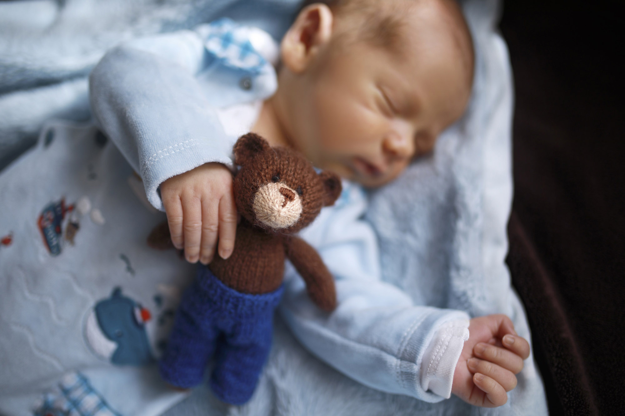 Sleeping infant with knitted toy