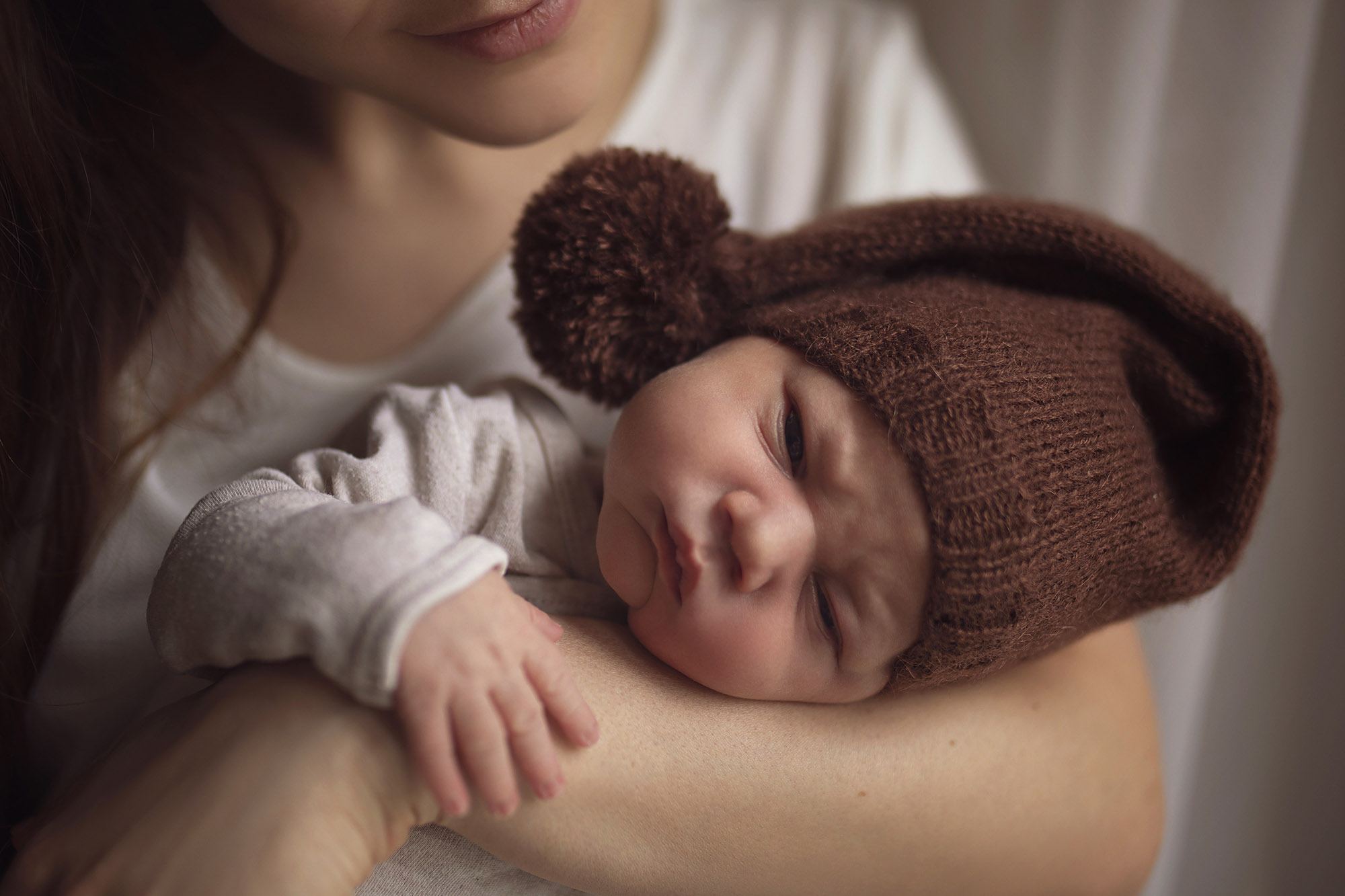 Mother holding an infant in a brown knit cap