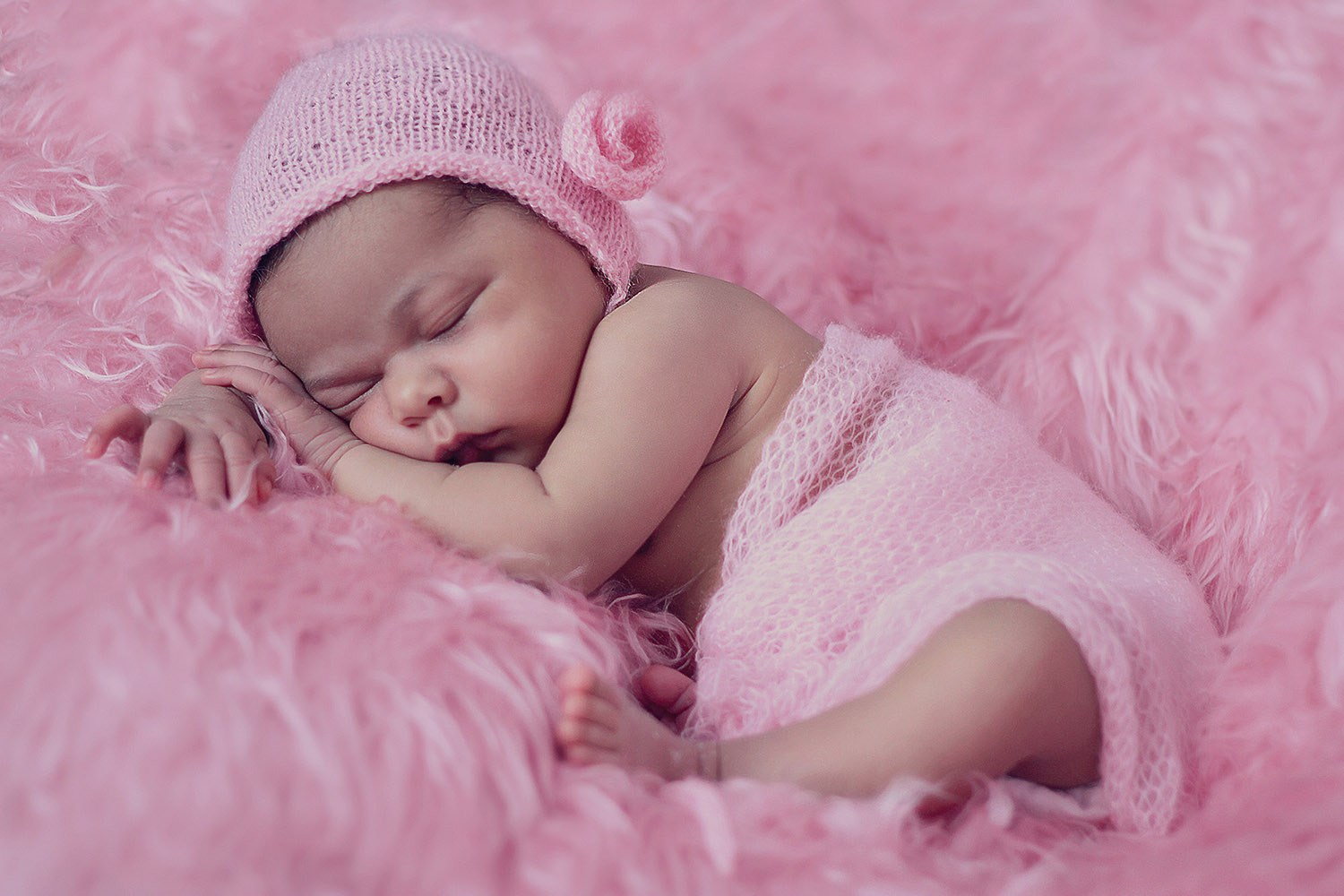Sleeping infant in knit cap on a pink fur