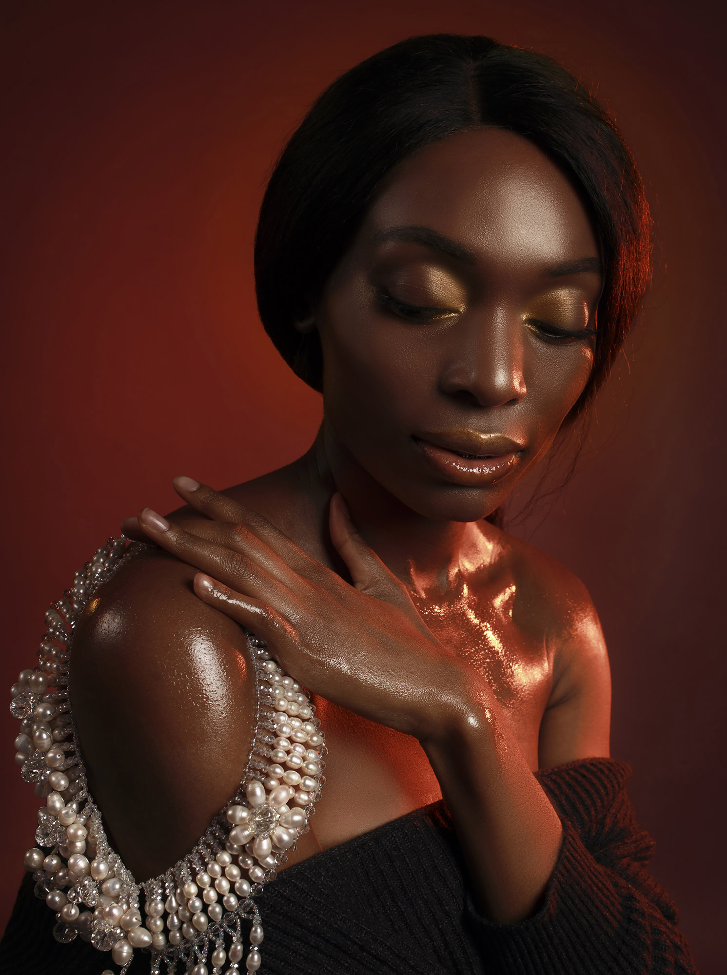 Black woman with white pearl on dark red background