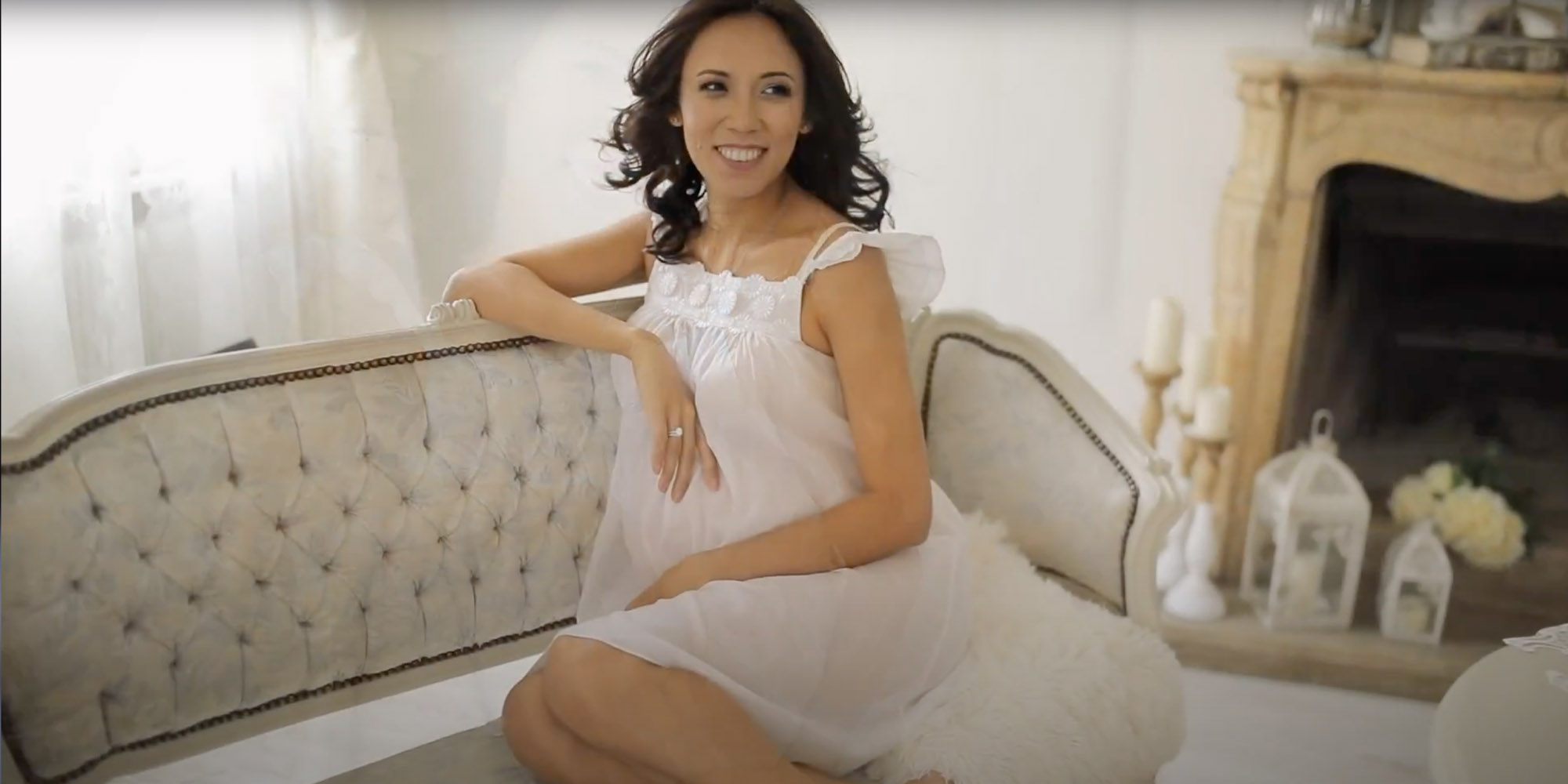 Pregnant woman sitting in a white couch near fireplace