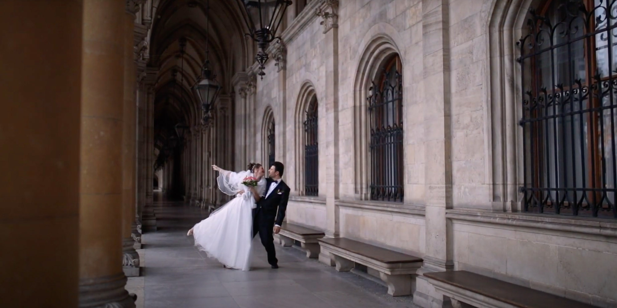 Married couple is dancing in medieval colonnade